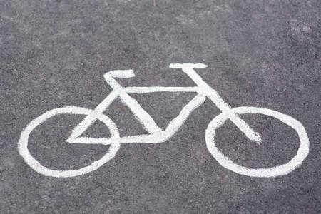 drawn symbol bicycle on asphalt bike path, road sign closeup on the ground.
