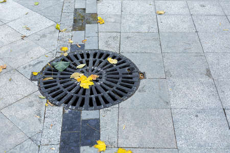 manhole cover round black metal lattice of improvement city park pedestrian sidewalk paved with granite gray tiles close-up view autumn season with fallen yellow leaves with copy space, nobody.