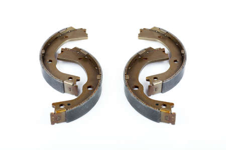 drum brake pads with asbestos alloy on a steel body of a spare part for a car isolated on a white background.