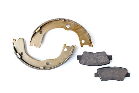 set of asbestos brake pads and brake shoe for disc and drum brakes, replacement spare parts of the car brake system isolated on white background top view, nobody.
