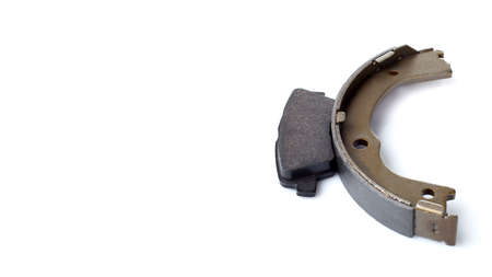 set of asbestos brake pads and brake shoe for disc and drum brakes, replacement spare parts of the car brake system isolated on white background with copy space banner, nobody.