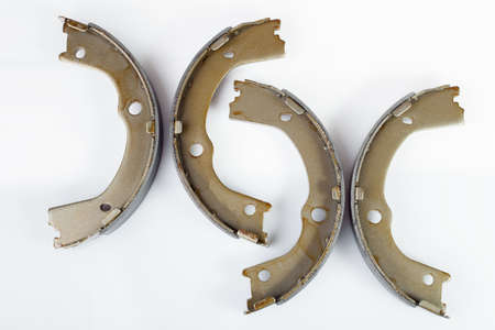 kit of drum brake pads with asbestos alloy on steel car spare parts isolated on white background side view.