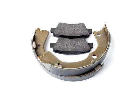 set of rear brake pads for disc brake and shoe for hand brake, new spare parts with brake lining material asbestos isolated objects on white background, nobody.