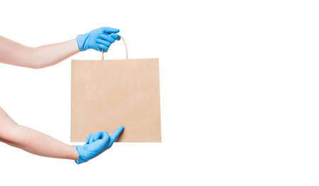 hands in sterile gloves of a courier for safe delivery of food in an eco friendly package points a finger to mock up isolated on white background banner with copy space. Stock fotó