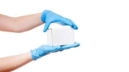 Delivery man hands in blue sterile gloves holds white label cardboard box, safe delivery during quarantine stay home, concept banner on medical theme isolated on white background with copy space. Stock fotó