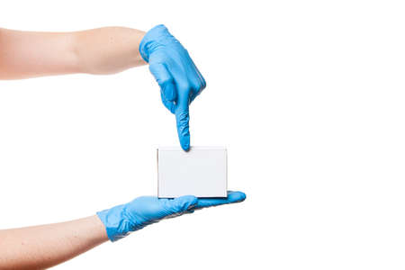 Delivery man hands in blue sterile medical gloves holds white label cardboard box on palm and shows finger, safe delivery during quarantine stay home, isolated on white background with copy space.