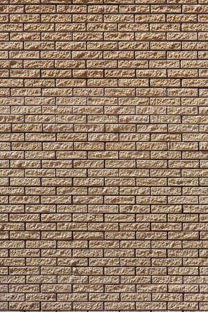 brick facade wall made of stone, beige texture of the building vertical background.