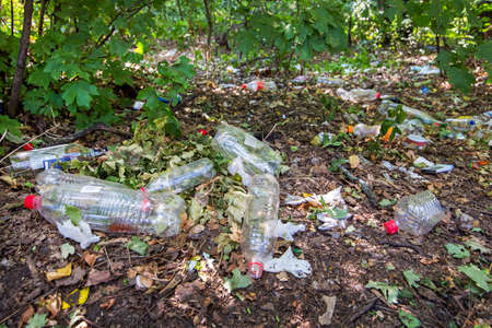 plastic bottles and plastic garbage in the forest on the ground pollutes nature, close-up of an ecological disaster closeup, nobody. Stock fotó