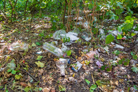 garbage dump made of plastic disposable products bottles and glasses with bags on the ground among the dying plants of mother earth closeup, nobody.