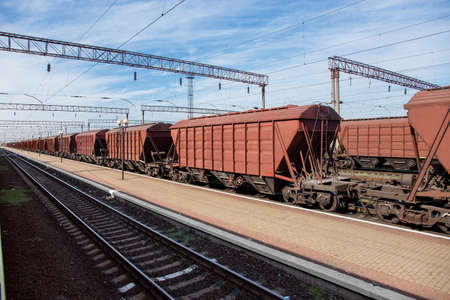 grain carrier freight car for transportation of bulk cargo of grain crops, railway track with rails and wagons going into perspective, background on theme of transportation and export of grain nobody. Stock fotó
