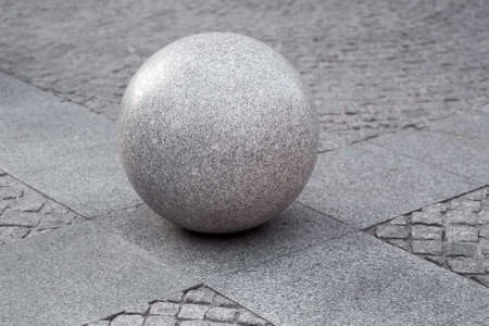 gray granite ball on the pedestrian sidewalk on a paving square with stone tiles, cityscape urban street architecture element, nobody.