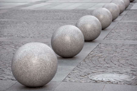row of glossy granite balls decoration traffic barrier on the sidewalk paved with square stone tiles, cityscape urban street architecture details with manhole, nobody. Banque d'images