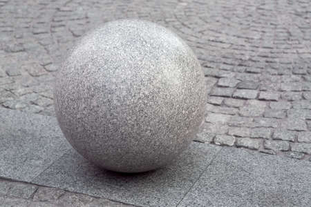 granite ball on the pedestrian sidewalk paved with stone tiles, cityscape urban street architecture, nobody.