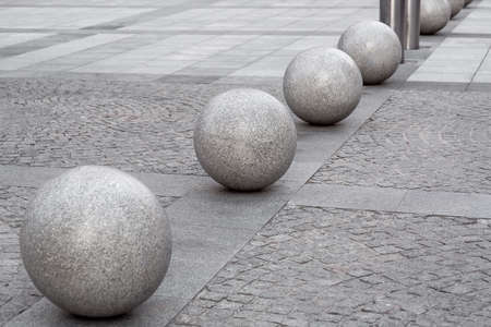 row of glossy granite balls decorative traffic barrier on the pedestrian sidewalk paved with square stone tiles, cityscape urban street architecture details, nobody. Stock fotó