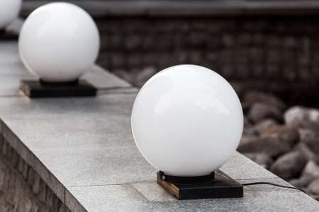 round ball street lighting on granite stone parapet on backyard terrace, lantern object close-up, nobody.