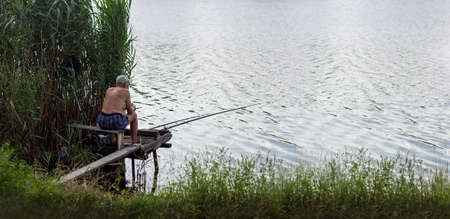 a male fisherman sits on a wooden bridge and fishes spinning in the river with water near the reeds on a summer day.