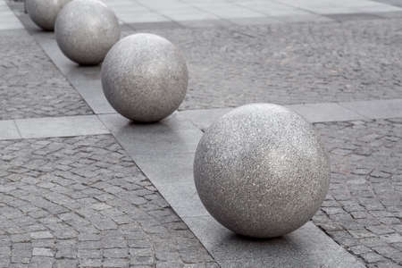 row of granite balls on the pedestrian sidewalk paved with stone tiles, cityscape urban street architecture, nobody.