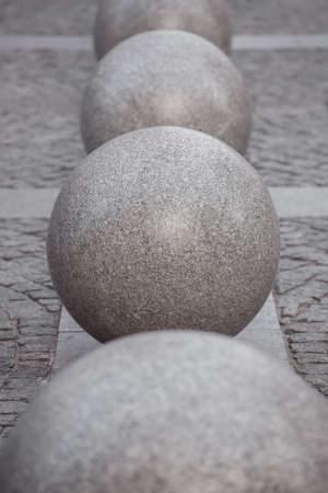 row of granite balls on the pedestrian sidewalk paved with stone tiles, cityscape urban street architecture objects, nobody.