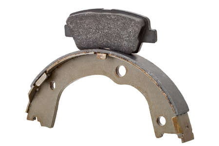 two kinds asbestos brake pads for disc brakes and shoe for drum brakes, replacement spare parts of the car brakes system isolated on white background, nobody.