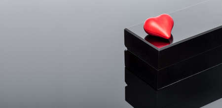 red volumetric heart lies on a black gift box on black glass with reflection, background on the theme of celebrating valentine's day.
