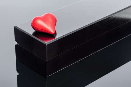 red shape volumetric heart lies on a black gift box on black glass with reflection, background on the theme of celebrating valentine's day.