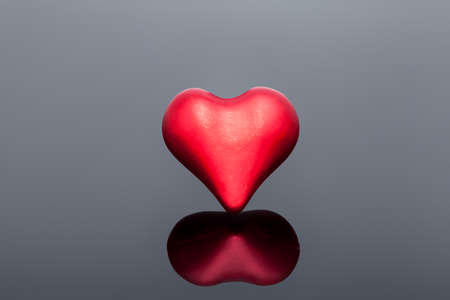 volumetric symbol of a heart of red on a black background with reflection, a symbol of health and love on the medical theme of celebrating Valentine's Day. Stock fotó