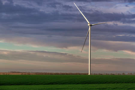 wind power generator in green hilly agricultural fields in the background sky with clouds, zero emissions renewable eco energy production in an outdoor farm.