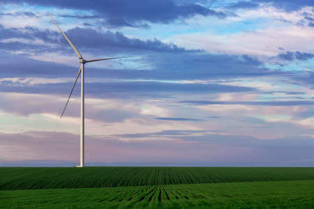 wind power generator in green hilly landscape in the background sky with clouds, zero emissions renewable eco energy production. Stock fotó