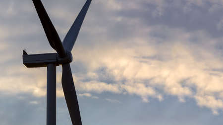 a wind turbine with blades generates environmentally friendly power close-up of a turbine against the sky with clouds. Stock fotó