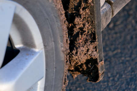 dirty car mudflap on the front wheel splashed with a mud closeup, tire with disk on a suv 4x4, nobody. Stock fotó