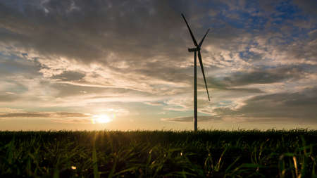 a silhouette of a wind turbine in a green field with grass against the backdrop of the sunset sky with the evening sun, eco power plant for the production of electricity. Stock fotó