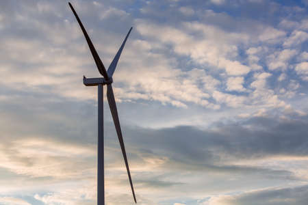 wind turbine offshore windmill of white color made of iron with blades side view against a blue sky with clouds on sunset, alternative electricity preserving nature.