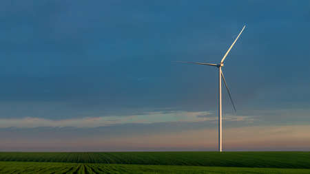 wind turbine in a green field in the hills of pure nature, eco-friendly electricity generation zero pollution on background blue sky with clouds, nobody. Stock fotó