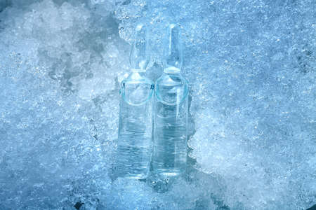 2 vaccine in glass ampoules with medical preparation for the treatment of covid viral disease is cooled to minus degrees in temperature lying on snow ice, cold background on medical.