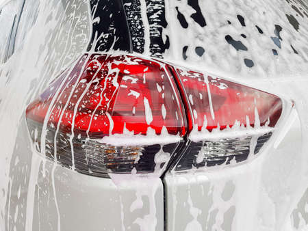 car taillight on back lid covered with active foam for washing a dirty car and wax, close up of the process of detailing vehicle care.