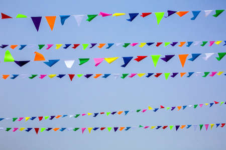 triangular festive multi-colored flags are suspended on a tight rope against the background of the sky, nobody. Banque d'images