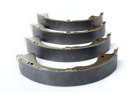 four brake shoes for drum brakes, spare parts for car consumables for service and maintenance of auto transport close up isolated objects on a white background asbestos alloy view, nobody.