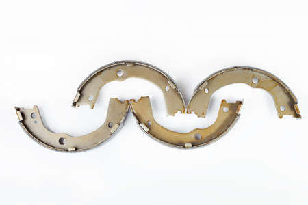 kit of four drum brake shoes with asbestos alloy on steel car spare parts pads isolated on white background top view, nobody.