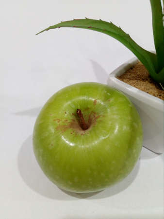 Apple with green leaf.