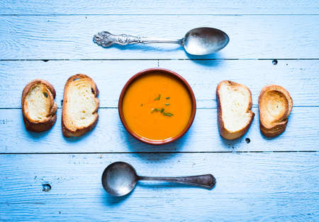Vegan Creamy Delicious  Pumkin Soup with fresh vegaetables and sliced of bread over a wooden background. Stock Photo
