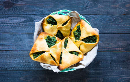 Spinach pie with ricotta cheese, on a wooden background.