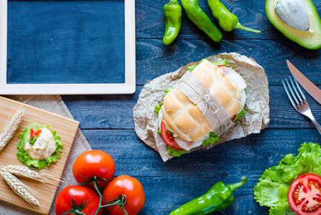 Fresh and tasty sandwich with ham and vegetables, isolated and tomato on wooden background Stock Photo