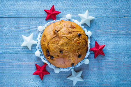 Panettone with fruit, orange, candied, raisins, and Christmas decoration, on a wooden background
