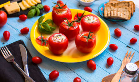 caper: Stuffed tomatoes with cheese, and different vegetables, on a wooden background, free space for text. Stock Photo