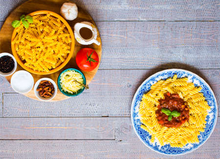 Fusilli pasta with tomato sauce, tomatoes, onion, garlic, dried paprika, olives, pepper and olive oil, on a wooden background. Top view