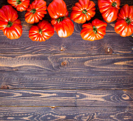 Ox heart tomatoes, on rustic wood background, free space for text. Top view Stock Photo