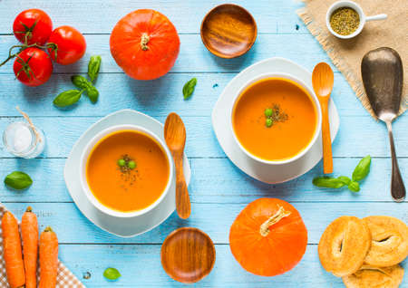 Homemade Pumpkin Soup on rustic wooden background, free space for text. Top view