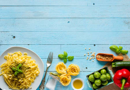 Pasta tagliatelle with pesto sauce and other vegetables on a wood background, free space for text. Top view