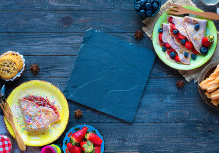 Fresh homemade crepes served on a plate with strawberries and blueberries, on a dark wooden background, free space for text.