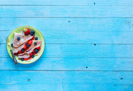 Fresh homemade crepes served on a plate with strawberries and blueberries, on a light blue wooden background, free space for text. Top view
